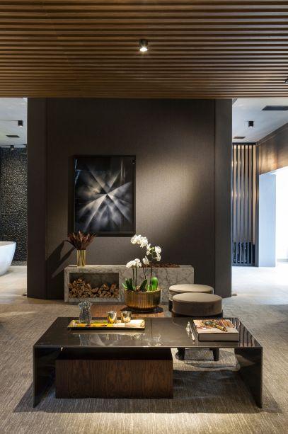 Loft do Designer - Alex Bonilha e Mahely Oliveira.No ambiente, destacam-se alguns elementos como a caixa amadeirada ripada nas paredes e teto do living, cores acinzentadas e o tom verde.
