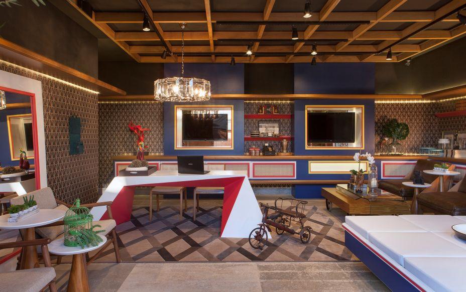 Lounge de Recepção - Lopes de Moura Studios. O espaço foi inspirado no Jockey Club de São Paulo. Os móveis trazem tons de madeira e cores primárias - vermelho, azul e amarelo. A mesa principal, desenhada exclusivamente para a mostra, é a protagonista do ambiente que abriga obras dos artistas plásticos Bia Doria e G. Comini.