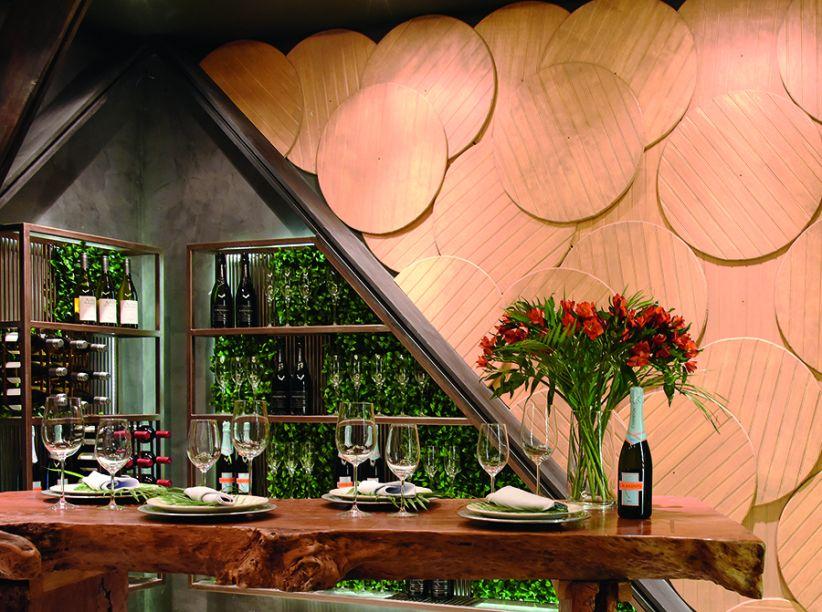 CAVA - ANDREA DELGADO E CAROLINA ROQUE. O antigo armazém frigorífico do restaurante deu lugar à cava, que conserva seu estilo industrial e inclui uma sala de degustação. A madeira é protagonista, na mesa de aparência rústica e na composição de placas que formam um painel.