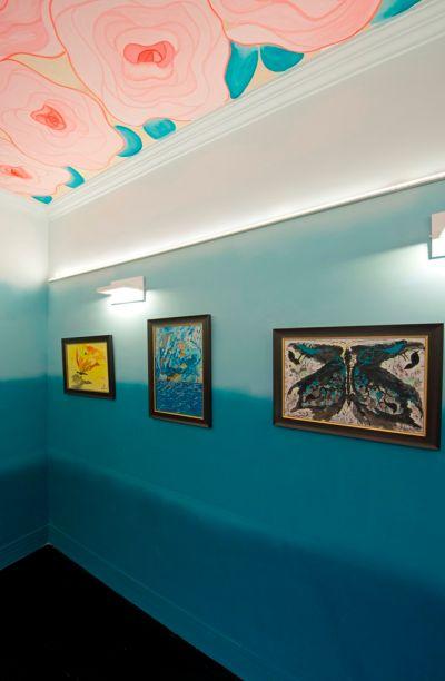 Galeria do Artista - A Essência das Rosas - Aline Gurgel. O olhar encontra no teto a obra do artista Filipe Benevides, em homenagem às Rosas de São Benedito. Nas paredes, o degradê de azuis é um pano de fundo tranquilo para a arte de Pedro Filho.