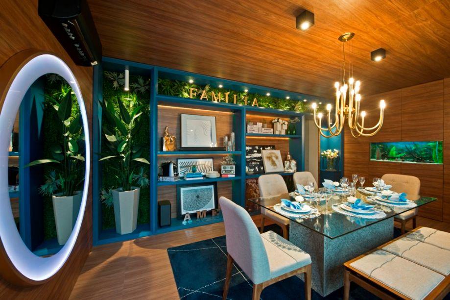 Sala de Almoço - Emanuelle Brito. O projeto se desenvolve a partir de uma caixa de madeira, que torna a ambientação envolvente e calorosa. Alguns recursos interferem para trazer leveza, como o aquário, o espelho com iluminação e a estante, que adiciona o azul à composição.