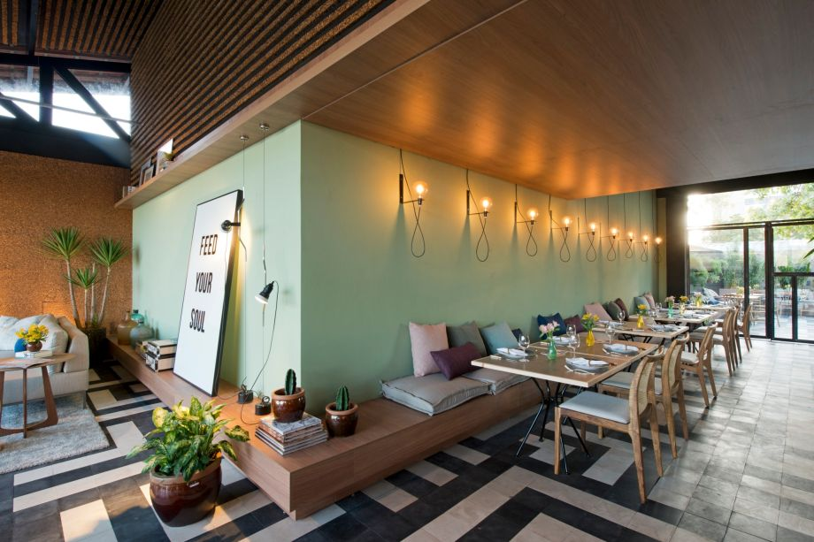 Restaurante Vida & Arte - Brenda Rolim. O forro acústico foi criado a partir de insumos de rolhas, desenvolvido pela arquiteta. Já o piso é um ladrilho hidráulico produzido de maneira artesanal. Outra inovação vem na proposta de uso compartilhado do espaço, sugerida pela extensa mesa.