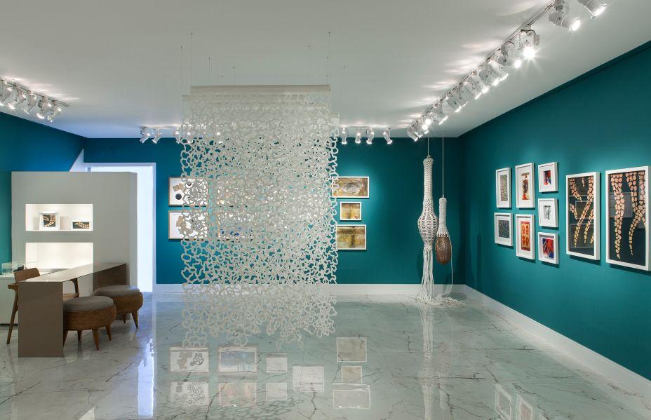 """<span style=""""font-weight:400;"""">Espaço Criativo Galeria - Adriana Zaneti e Aurea Ligia Bernardi. A arquitetura deste projeto foi pensada para realçar o design contemporâneo que permeia o espaço. O piso, de revestimento cerâmico, mantém uma conversa intimista com o teto, enquanto as cores e rodapés alinham a dimensão espacial para receber as peças expostas. Destaque para a iluminação, criada para estimular o sentido do observador. </span>"""