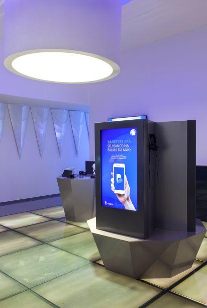 """<span style=""""font-weight:400;"""">Espaço Digital Banestes - Karla Giaretta e Levy Netto. A experiência sensorial é explorada no ambiente de 60 m², que abriga equipamentos tecnológicos e interativos do banco. As formas geométricas e as cores neutras completam a atmosfera futurística, como no piso, parcialmente retroiluminado e nos revestimentos da parede.</span>"""