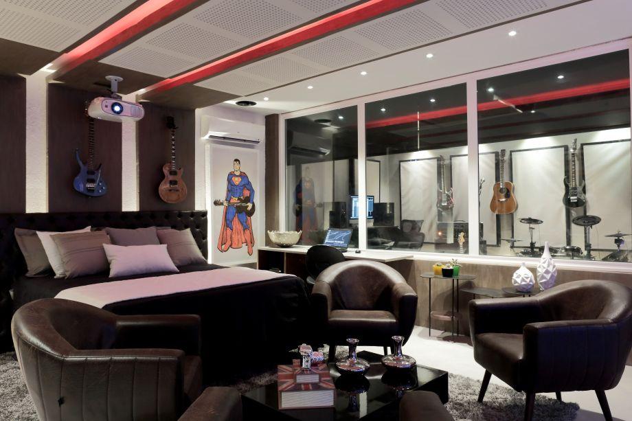 Suíte Music - Eduardo Henrique. A completa fusão entre um quarto multimídia e um estúdio de produção musical. Uma grande esquadria de vidro duplo isola os ruídos entre os ambientes. O mobiliário e os revestimentos seguem o conceito high tech.