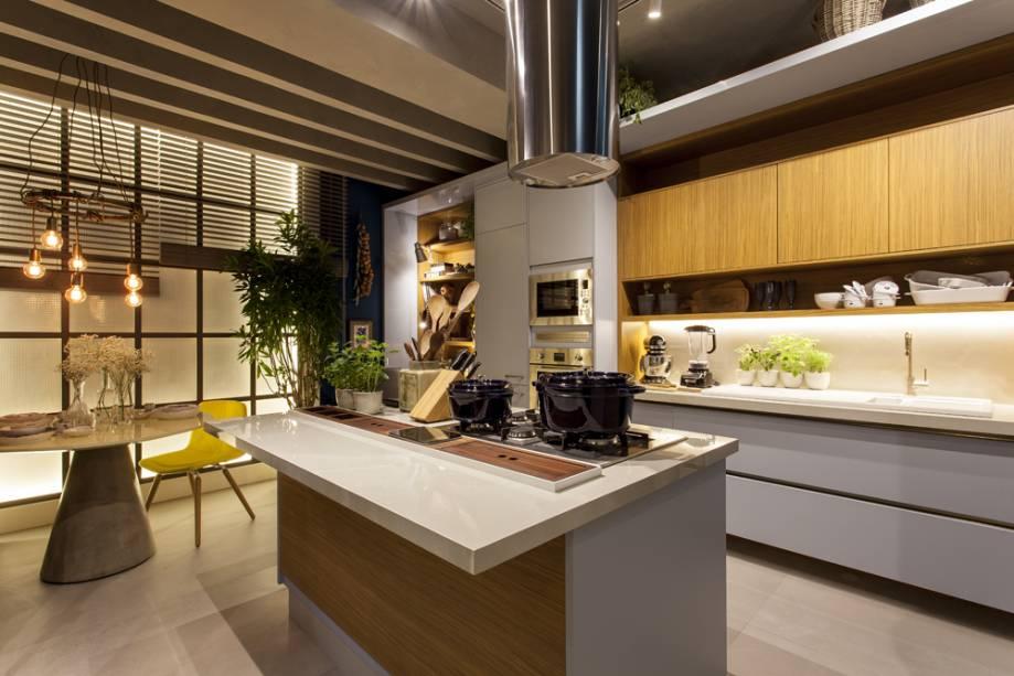 <span>Copa Cozinha - Thiago Manarelli e Ana Paula Guimarães. O espaço é composto por três ambientes: um canto com poltrona para leitura, a copa com sofá, mesa e duas cadeiras e a ilha com duas banquetas. A madeira clara dá o tom para a paleta de cores neutras que aquece a Cozinha.</span>