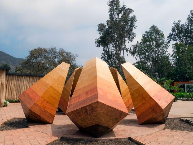 PATIO DEL ENCUENTRO - JUAN SEBASTIÁN RICO. Cinco pirâmides em madeira orbitam em um jardim circular e desafiam a gravidade, unidas pela base. A matéria-prima natural é destacada, para trazer a mensagem de preservação e da importância da certificação da madeira. As esculturas também emitem luzes e sons, criando outras conexões com os visitantes.
