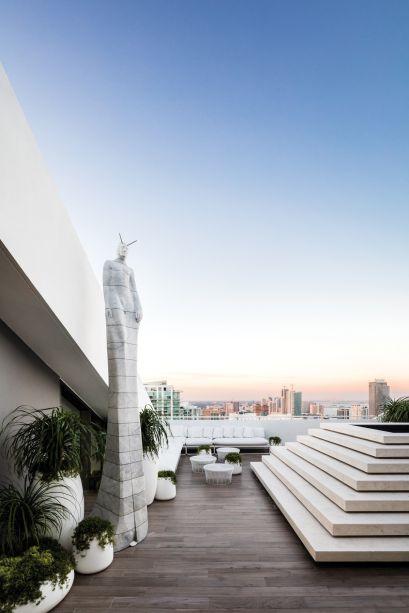 """Sky Line Penthouse Garden - Fernando Wong. """"É como se o espaço estivesse flutuando acima da cidade"""", define o profissional, que imaginou um jovem casal recebendo seus convidados em um terraço tropical. A leveza vem dos diferentes tons de branco em móveis, acessórios e na estátua de mármore do artista italiano Oriano Galloni."""