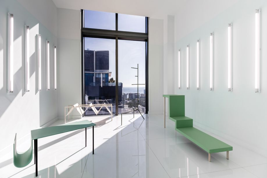 Office GA - Jonathan Gonzalez. O quarto padrão foi transformado em um cenário de galeria, que exibe sobre um fundo branco exemplares de arquitetura e mobiliário geométrico. Peças de iluminação lineares desenham listras que interferem nas superfícies - até então neutras.