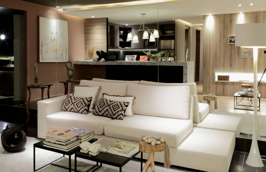 CASACOR Alagoas: Compacto, esse sofá branco e reto é o essencial para um apartamento de 70 m<span>²</span> como este. Seu tom claro e o espelho ao fundo dão a sensação de amplitude para a sala do Apartamento Mares do Sul 2. Ceres Vasconcelos investiu numa decoração minimalista para não faltar espaço para receber os amigos.