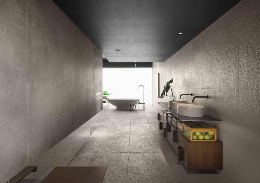 CASACOR Brasília: Sala de Banho - Priscila Gabriel. O minimalismo é bem representado no ambiente de 78m² e o cimento é um dos poucos materiais utilizados. Repare ainda na bancada slim, que apoia as cubas e é complementada pelo móvel em madeira. Tudo valoriza a experiência do banho de forma sensorial e natural.