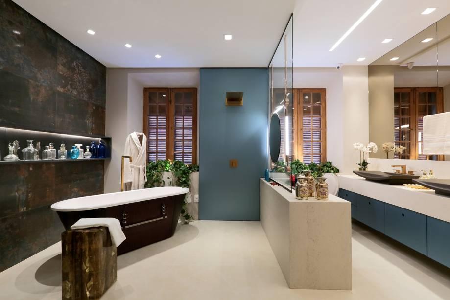 CASACOR Pernambuco: WC do Casal - Marcelo Teixeira. É um espaço rústico e elegante ao mesmo tempo. Ele é equipado com cuba dupla, banheira, área para chuveiro separada e penteadeira, todos com linhas simples e traços em dourado. (