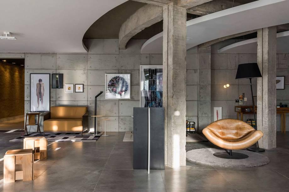 CASACOR Brasília. Bilheteria/Galeria Meia 1 - Debaixo do Bloco Arquitetura. O concreto está no DNA de Brasília, assim como o branco da arquitetura de Niemeyer. São esses os elementos chave, em uma linguagem que revela as imperfeições e a autenticidade do espaço. De forma pontual, foram inseridos móveis brasileiros e obras artista Christus Nobrega, distribuídos nos 105m².