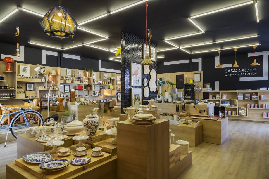 CASACOR SP: Marton Estúdio - Loja da CASACOR. José Marton buscou inspiração em lojas de grandes museus, como o MoMA, em Nova York, e o Centre Pompidou, em Paris. Com poucos materiais - basicamente melamínico madeirado e pastilhas em vidro -, foram trabalhadas as formas e a repetição em linguagem minimalista. Tudo para destacar os produtos, os verdadeiros protagonistas.