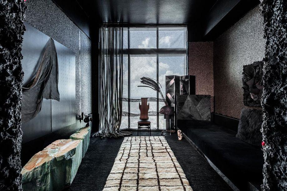 CASACOR Miami. Skēnē Studio - Gustavo Neves. Com referências à soprano Maria Callas, o projeto investe na dramaticidade. Revestimentos escuros nas paredes, pontilhados em metal, cordas e armários em pedra criam esse mood, além do tapete branco com linhas pretas, um ponto de atração do olhar no espaço.