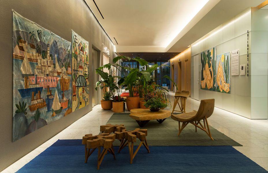 CASACOR Miami. Tarsila Hall copyright © Tarsila Empreendimentos - Paulo Alves Design. O lobby do elevador foi convertido em galeria de arte, com paredes que exibem tapeçarias inspiradas em pinturas famosas da modernista Tarsila do Amaral. Os tapetes de várias cores completam o décor.