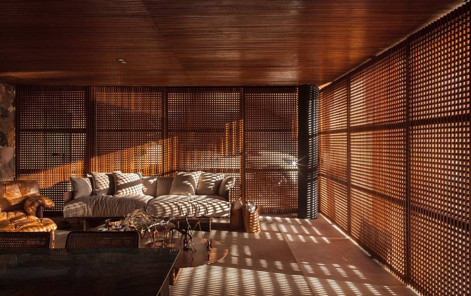 CASACOR Franca.<span>Recanto do Colecionador | Loft Renault - mf+arquitetos.</span><span>Os brises pivotantes de madeira fecham a casa e permitem a entrada de luz que cria padrões geométricos ao longo das superfícies interiores. O jogo de sombras conversa com as paredes da cozinha e do banheiro, cobertas por mármore escuro e branco.</span>