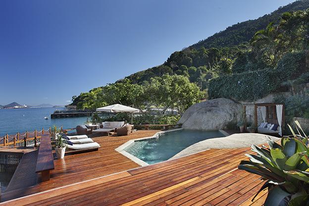 Paola Ribeiro - Casa em Angra dos Reis. Na encosta do morro, de frente para o mar, a piscina de formato abstrato se assemelha a um lago natural.