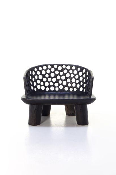 Carvel 07, de Paola Navone para Gervasoni. A cadeira com braços, feita de mogno e esculpida a mão, parece uma escultura tribal. O assento é curvado e o encosto tem perfurações semi-circulares.