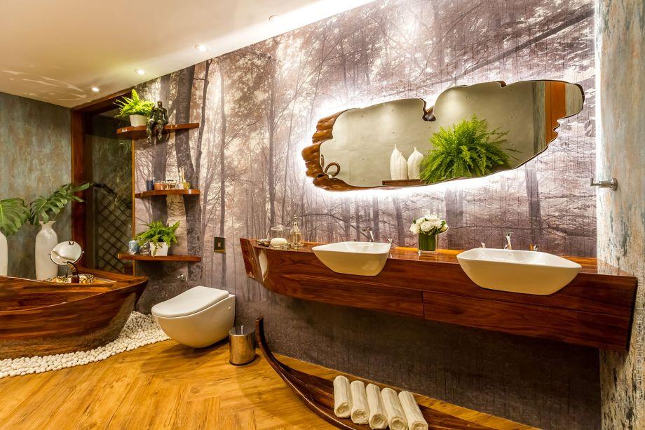 CASACOR Bolívia.Baño Rilassante - Rudy Rivero e Sofía Suárez. Um encontro entre elementos modernos e materiais naturais. A banheira foi esculpida em madeira, como uma obra de arte, e o espelho é recortado como um elemento orgânico. A parede principal define o cenário, com a imagem impressa de floresta.