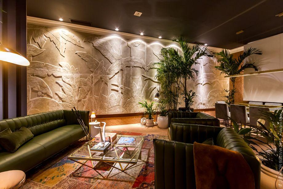 CASACOR Bolívia.Living Principal - Roberto Franco. Iluminação dramática e layout descontraído são os pontos de partida e evocam o glamour dos anos 1930 em Miami. No chão, um porcelanato rústico. Na parede, um mural tropical em gesso, de fabricação artesanal.