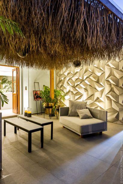 Casa Deca - Milagro Lecuona e Patricia Barrón. A paleta de cores suaves proporciona uma integração ainda mais natural entre a casa e o entorno. Destaque para a volumetria marcante do telhado em palha e da parede iluminada. Para equilibrar, móveis trazem o essencial nas formas.