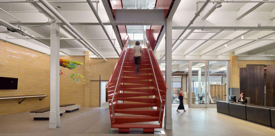 O lobby conta com novas escadas, tijolos e móveis reutilizados.