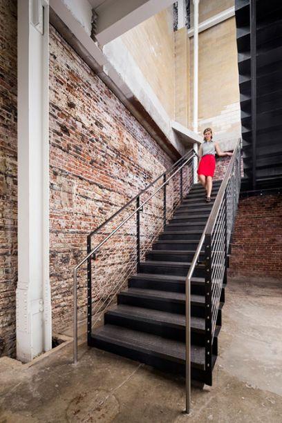 Tijolos interiores e exteriores lembram que o uso original da construção era de uma fábrica.