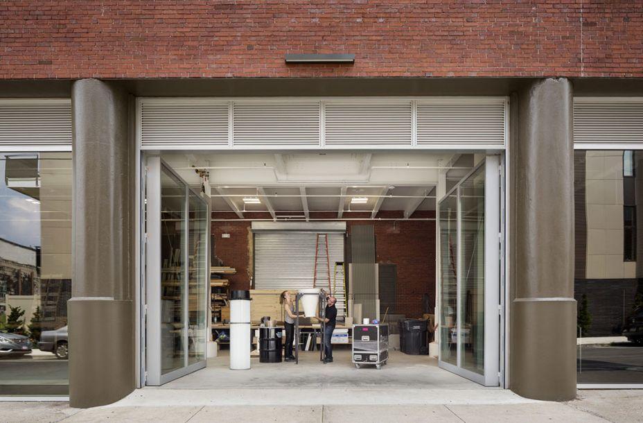 Com altas portas de vidro que abrem a a rua, a oficina pode receber grandes materiais facilmente.