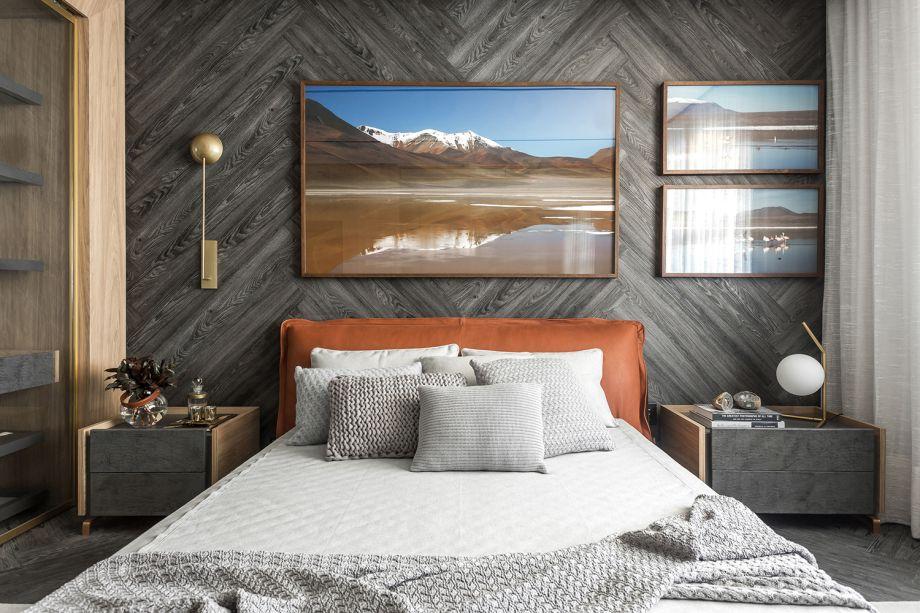 Suíte de Hóspedes - Alessandra Gandolfi. Neste refúgio, o ponto central é a cama da Natuzzi Itália, estofada em couro no tom de telha. O piso foi aplicado na parede, compondo o padrão espinha de peixe. Fotografias e telas remetem ao desejo de reconexão com a natureza.
