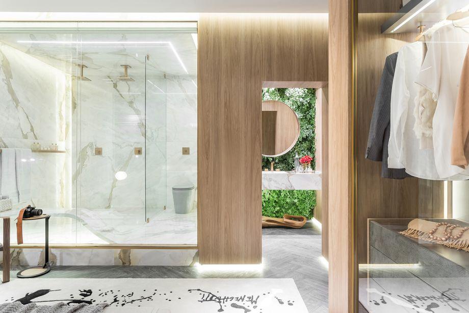 CASACOR Paraná 2018. Suíte de Hóspedes - Alessandra Gandolfi. Neste quarto, a sala de banho é uma caixa em mármore, conectada visualmente ao closet, delimitado com painéis de madeira. Na parede que acomoda a bancada, o jardim vertical traz vida para o espaço.