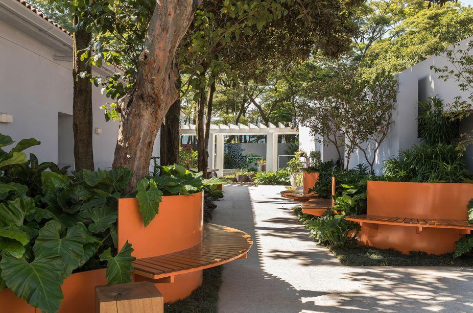 Coliving - Clariça Lima. Os bancos em aço corten trazem um contraste de cor bem-vindo, em meio à vegetação que abraça e convida a uma pausa. Nas poucas paredes do local, foi aplicada uma pintura ombré.