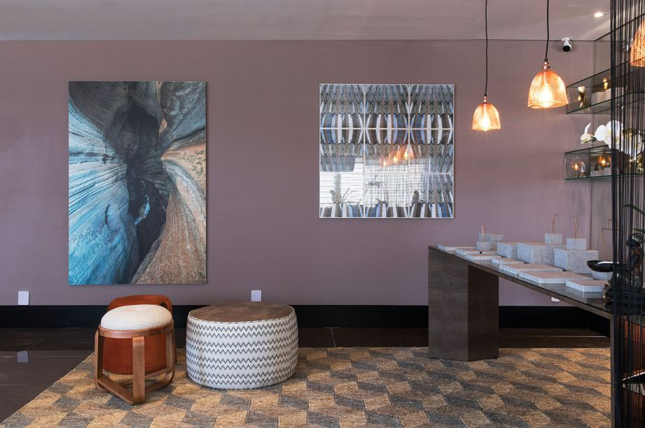 Lounge de Saída - Denise Monteiro. O crochê é um elemento fundamental e inspira a adoção de outros elementos gráficos, como o mosaico de madeira em uma das paredes. A combinação de tons claros e terrosos cria uma atmosfera calma, que convida a permanecer.