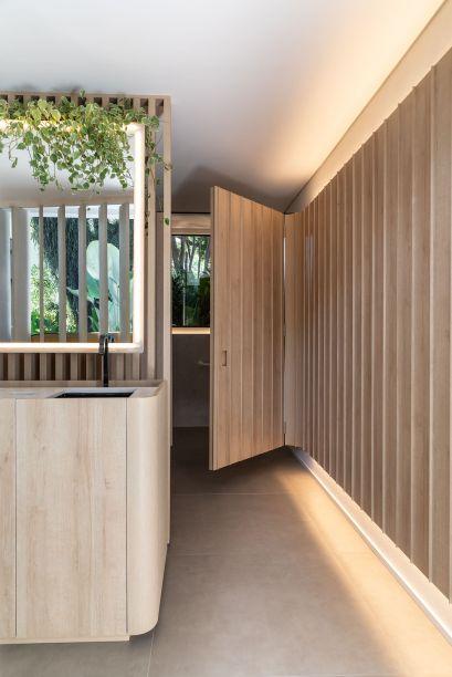 Recinto do Bosque - GDL Arquitetura. Partindo de um retângulo modular, Gabriel de Lucca projetou um banheiro conectado ao exterior por meio de fendas na parede. Elas também permitem a incidência de luz solar, dispensando o uso de pontos de iluminação no teto. Na marcenaria, destaque para o alinhamento preciso entre retas e curvas.