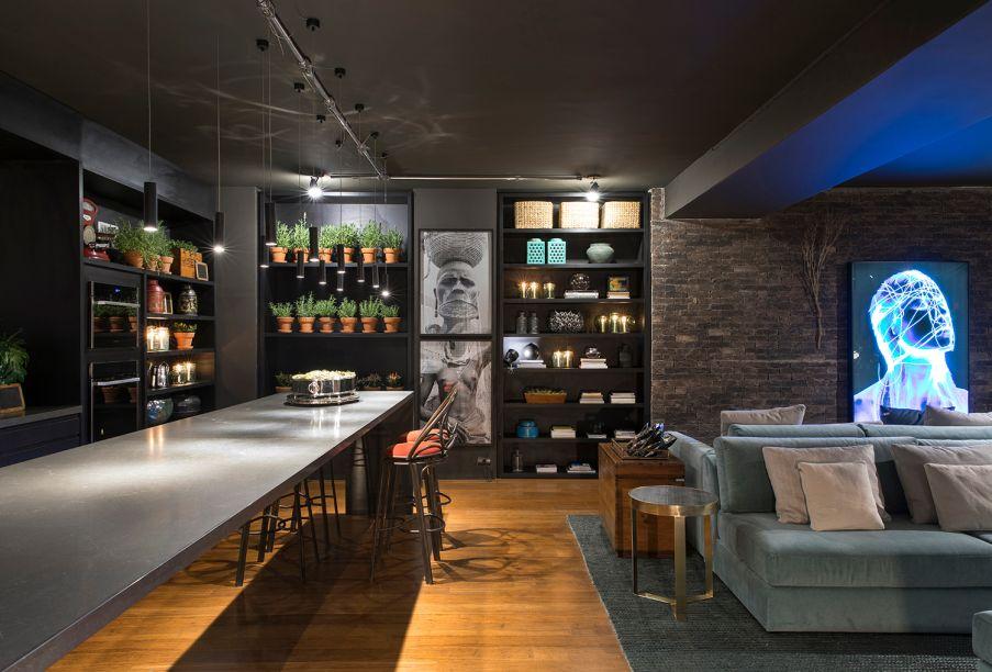 Lounge Sensações™ - Gustavo Paschoalim. A cozinha gourmet é integrada ao amplo living, totalizando 92 m². Com a pegada dos lofts americanos, utiliza piso de demolição de bambu, iluminação em trilhos aparentes e tijolos ingleses nas paredes. A decoração é exposta nas estantes e inclui objetos dos séculos 18 e 19. O estilo prático se confirma na mesa extensa e multifuncional. Para suavizar, estofados azuis.