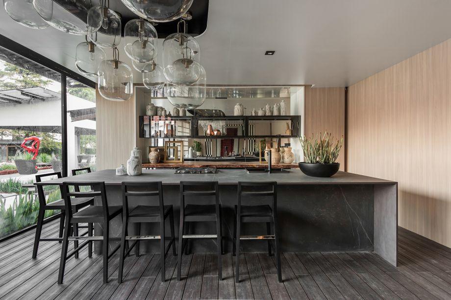 Galeria Gourmet Compagas - Ivan Wodzinsky. Sala de jantar e uma cozinha-show são reunidos, com um estilo nômade e caloroso. A mesa é generosa e propicia a interação, para receber os convidados e as aulas dos chefs. As cores e texturas remetem ao brutalismo, enquanto detalhes em aço, dekton e espelhos representam o design sensitivo. A transparência está literalmente em alta, na luminária-instalação.