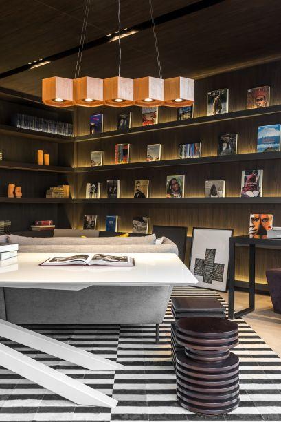 A Livraria, assinada por Katleen Luizaga, utiliza um tapete listrado clássico, nas cores preto e branco para criar uma atmosfera convidativa aos leitores.