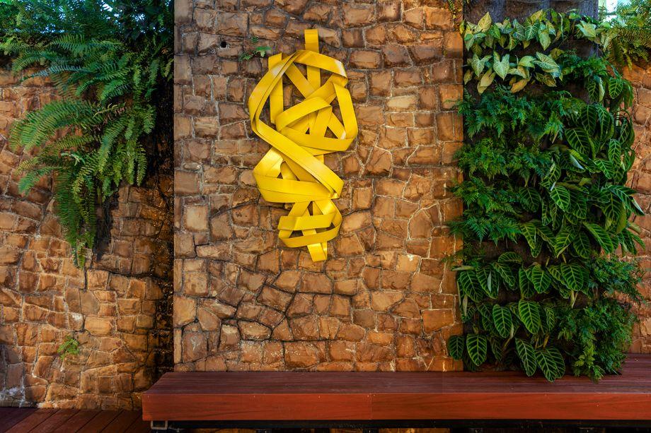 Alameda -Mauro Contesini. A parede existente no local serve de pano de fundo para o ambiente de 96 m². No banco em madeira, o visitante permanece mais tempo e se desconecta da vida urbana, apreciando as espécies selecionadas pelo paisagista. Entre elas, nandina, bromélia fireball e lisimáquia.