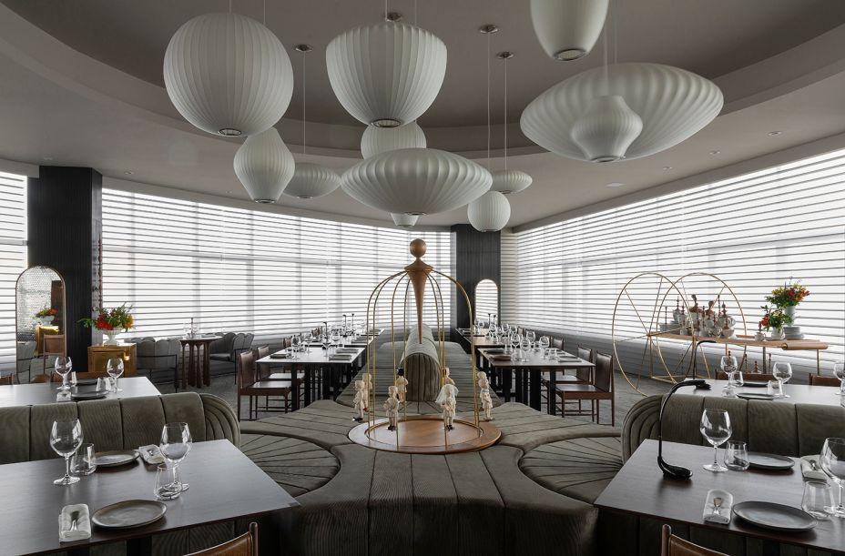 """O layout do Restaurant se desenvolve ao redor do grande sofá em formato de """"Y"""", projetado por Leo Romano, que também assina o ambiente. O móvel define as posições das mesas, junto com cadeiras Cantu, de Sergio Rodrigues. Leo também desenvolveu a identidade visual das louças em parceria com a artista e designer Ieda Jardim."""