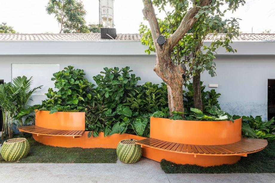 A paisagista Clariça Lima, desenhou para o <strong>Coliving</strong> o Banco Floreira, com a finalidade de proteger e abraçar as árvores já existentes no Jockey. As peças foram executadas com chapa metálica pintada na cor laranja e com assentos em ripas de madeira cumaru.
