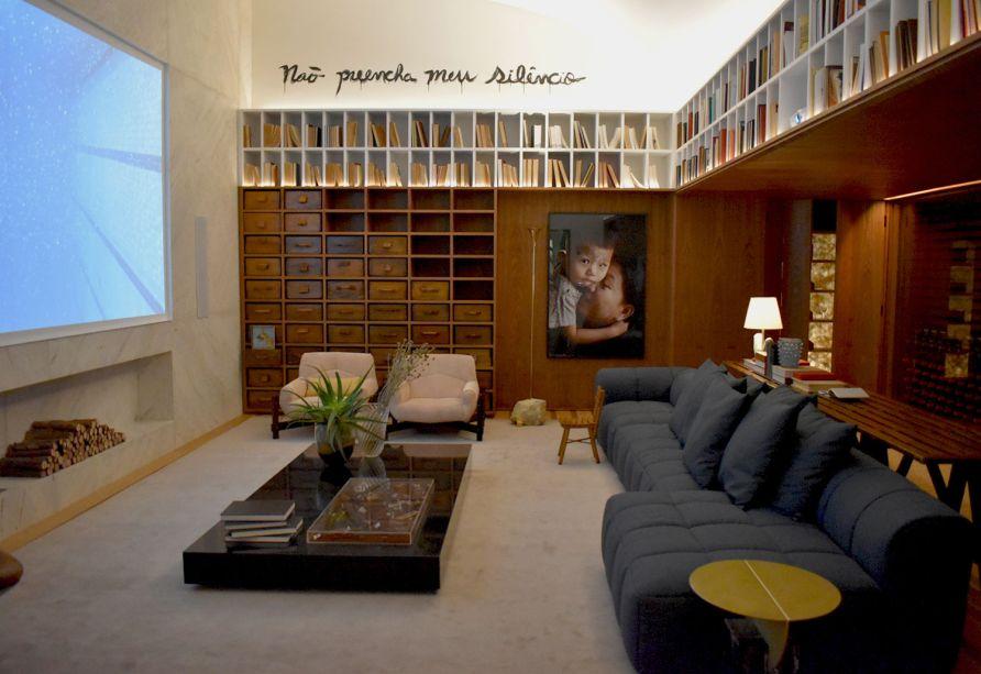 BC Arquitetos – Home Family. A biblioteca é um local de silêncio. O profissional optou por uma frase arrebatadora, que suscita a reflexão do visitante em um espaço extremamente intimista e aconchegante.