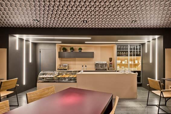 Café - Gisela Miró e Rafael Carvalho. Apesar de o protagonista aqui ser o papel de parede do teto, a madeira empregada de forma contemporânea, em tonalidades vivas, reforça a atmosfera cosmopolita do ambiente.