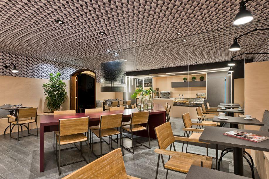 No Café, assinado por Gisela Miró e Rafael Carvalho, o grande espelho que cobre a parede cria, além da sensação de amplitude, um efeito visual instigante com o padrão geométrico do teto.