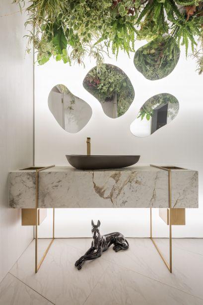 Toillete Masculino - Camila Rocha e Monica Pajewski. Iluminação e mármore branco tornam do espaço um local de aparência leve e clara. Os toques dourados marcam o mobiliário e trazem pontos de luz que prendem o olhar.
