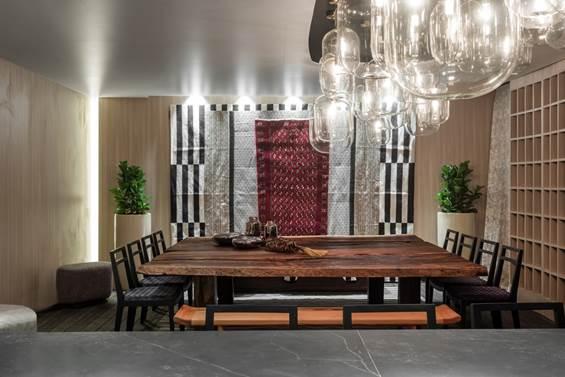 CASACOR Paraná.Galeria Gourmet Compagas - Ivan Wodzinsky. Sala de jantar e uma cozinha-show são reunidos, com um estilo nômade e caloroso. A mesa é generosa e propicia a interação, para receber os convidados e as aulas dos chefs. As cores e texturas remetem ao brutalismo, enquanto detalhes em aço, dekton e espelhos representam o design sensitivo. A transparência está literalmente em alta, na luminária-instalação.