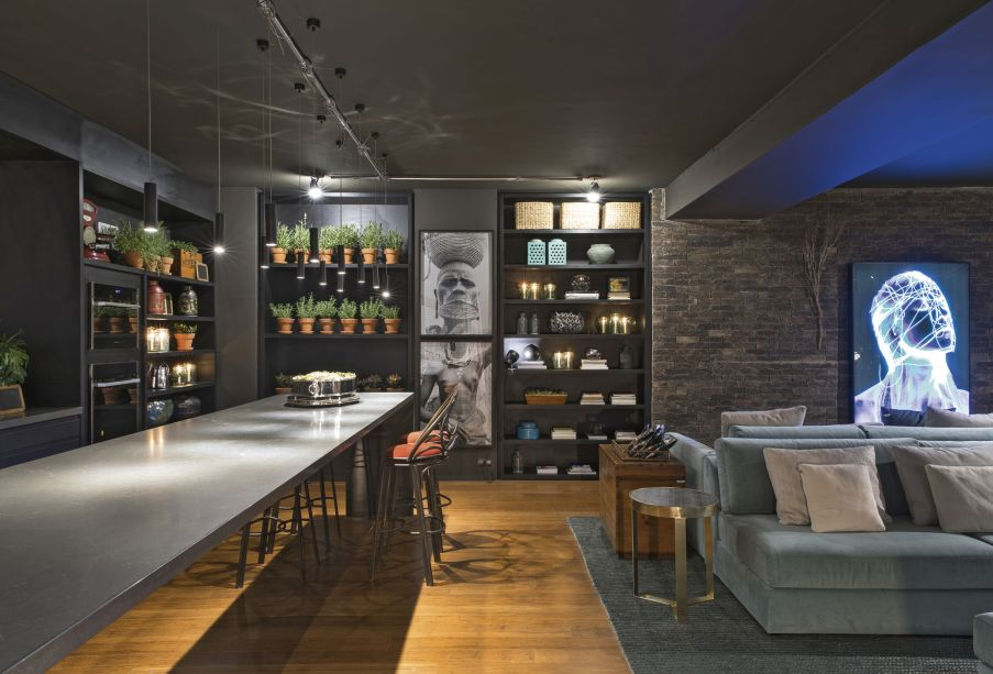 <span>Gustavo Paschoalim - Lounge Sensações™. A cozinha gourmet é integrada ao amplo living, totalizando 92 m². Com a pegada dos lofts americanos, utiliza piso de demolição de bambu, iluminação em trilhos aparentes e tijolos ingleses nas paredes. A decoração é exposta nas estantes e inclui objetos dos séculos 18 e 19. O estilo prático se confirma na mesa extensa e multifuncional. Para suavizar, estofados azuis.</span>