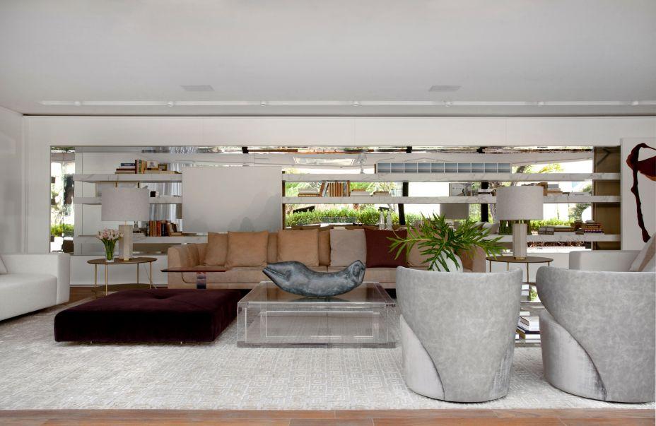 """<span style=""""font-weight:400;"""">Casa Linea - Lídia Maciel. A enorme estante de mármore serve de apoio para livros e ainda é o encosto do sofá, além disso, recebe um espelho ao fundo, que amplia toda o espaço e reflete a vista para o jardim.</span>"""