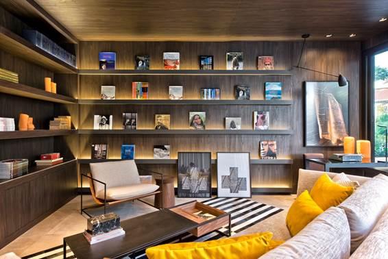 Livraria - Katleen Luizaga. A estante planejada, neste ambiente dedicado à leitura, ganhou revestimento em MDF nas paredes, ao fundo, e no teto. Em conjunto com os LEDs, o material cria um um cenário exclusivo, onde os livros são de fato os protagonistas.