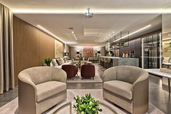 Lounge 25 Anos CASACOR Paraná - Viviane Loyola. Neste ambiente comemorativo, os painéis de madeira trazem aconchego. Aliados ao mobiliário com tecidos claros e tons de dourado, o espaço ganha ainda mais sofisticação.