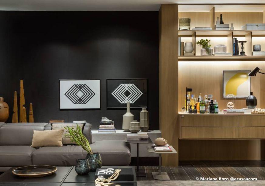 Em forma de quadros acima do sofá, estão os geometrismos da Casa Carbono, assinada por Pedro Tessarollo e Jairo Lopes. As linhas e o contraste entre o preto e o branco dão um toque especial à parede preta do espaço.
